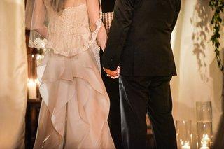bride-in-oscar-de-la-renta-groom-in-tommy-hilfiger-hold-hands-during-ceremony
