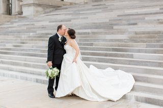 bride-in-justin-alexander-plain-ball-gown-holds-train-kisses-groom-in-menguin-suit