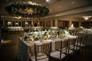 wreath-of-flowers-over-dance-floor-linens-beige-gold-chairs-low-centerpieces-on-rectangle-tables