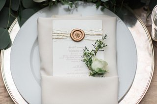 wedding-reception-menu-with-gold-wax-seal-metallic-strands-with-white-rosebud-in-white-napkin