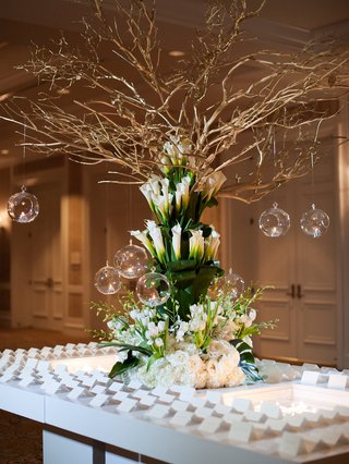 wedding-reception-white-table-with-large-arrangement-of-greenery-white-flowers-calla-lily-branches