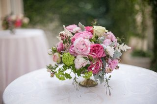 patterned-round-cocktail-table-with-small-flower-arrangement-of-pink-flowers-by-marks-garden