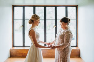 blonde-bride-with-low-chignon-bun-holds-hands-with-mother-of-the-bride-in-neutral-dress
