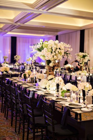 white-and-green-flowers-modern-reception-decor-ballroom-wedding-purple-lighting-black-chairs