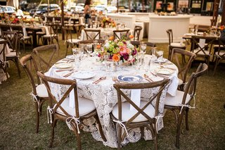 wood-charis-with-white-cushions-textured-ivory-linen-vibrant-low-centerpiece-rose-gold-flatware