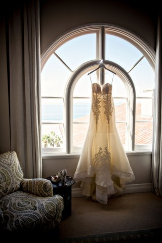 ines-di-santo-wedding-dress-hanging-in-window-of-casa-del-mar-bridal-suite-lace-strapless-appliques