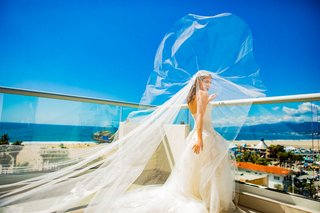 bride-in-monique-lhuillier-wedding-dress-and-veil-blowing-in-wind-ocean-view-balcony