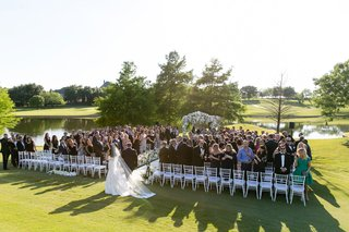 bride-with-veil-walking-with-father-of-bride-toward-aisle-dallas-wedding-golf-course-white-chairs