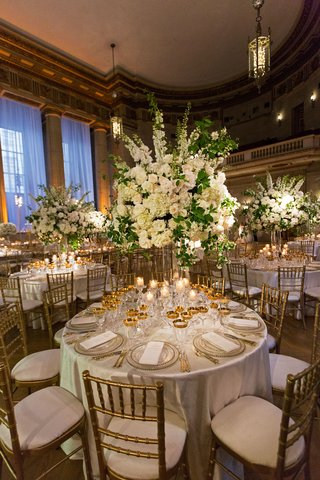wedding-reception-round-table-gold-chairs-gold-glassware-tall-centerpiece-white-flowers-greenery
