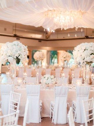 drapery-and-chandelier-over-dance-floor-blush-linens-white-flower-centerpieces-and-chair-covers