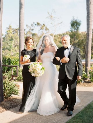 bride-in-a-line-wedding-dress-veil-over-face-walked-down-aisle-by-mother-in-black-dress-and-father