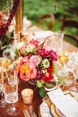 wedding-reception-table-with-small-bouquet-of-pink-red-and-magenta-flowers-with-a-thin-red-feather