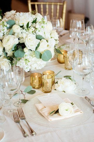white-floral-centerpiece-trio-of-gold-votives-bloom-on-napkins