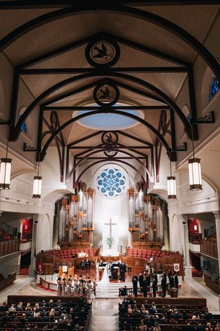 bride-and-groom-at-altar-traditional-church-ceremony-with-high-ceilings-pews-guests-wedding-party