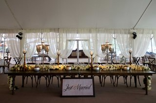 tented-wedding-reception-with-long-wood-head-table-rose-table-runner-just-married-sign-candelabra