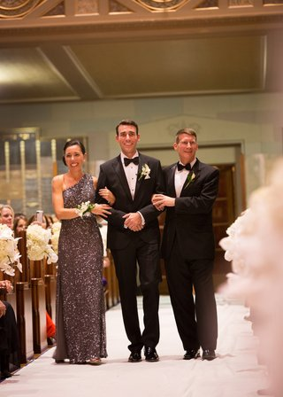 groom-in-a-black-tuxedo-walks-down-the-aisle-with-parents