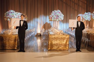 wedding-reception-table-number-idea-have-male-models-in-tuxedos-hold-table-numbers-for-guests