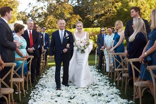 bride-in-classic-wedding-dress-with-pink-dahlia-bouquet-father-of-bride-white-flowers-on-grass