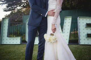bride-and-groom-pose-at-wedding-venue-lace-white-mermaid-dress