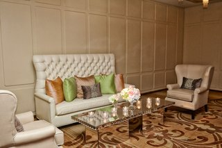 wedding-reception-lounge-area-with-tufted-sofa-mirror-table-candles-green-pink-throw-pillows