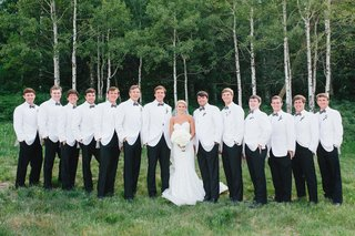 bride-in-inbal-dror-wedding-dress-with-groomsmen-and-groom-in-white-tuxedo-jackets-bow-ties