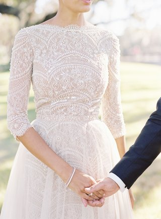 lace-wedding-dress-with-diamond-engagement-ring-and-two-dainty-bracelets-holding-hands-with-groom