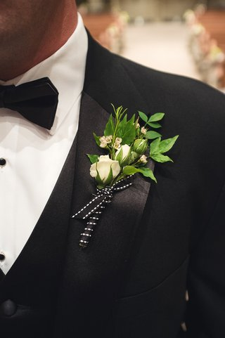 wedding-boutonniere-of-white-flowers-and-leaves-tied-with-black-ribbon
