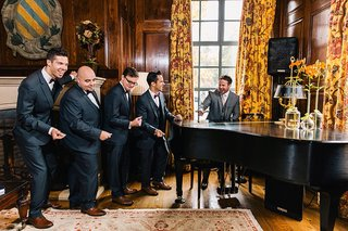 groom-and-groomsmen-playfully-act-out-a-performance-in-their-tuxedos-with-piano