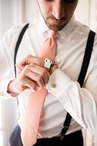 wedding-photo-of-groom-getting-ready-suspenders-pink-tie-silver-watch-and-cuff-links