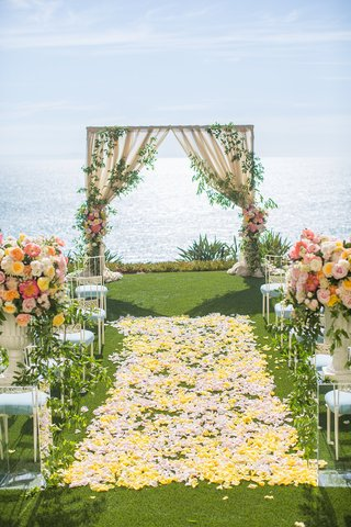 wedding-ceremony-aisle-yellow-flower-petals-arch-with-greenery-ocean-view-laguna-niguel