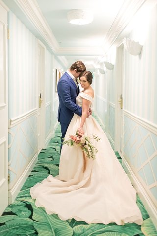 bride-in-off-the-shoulder-blush-ball-gown-and-groom-in-navy-blue-suit-in-hallway-of-the-colony-green