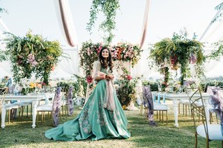 bride in green ball gown wedding reception dress flower print design at reception tent