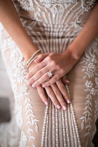 bride in adam zohar wedding dress light pink nails manicure with cushion cut engagement ring