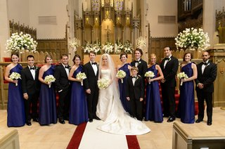 bride-and-groom-at-church-with-blue-bridesmaids-and-tux-groomsmen
