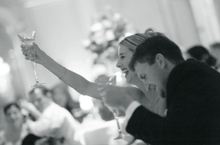 black-and-white-image-of-couple-toasting-at-reception