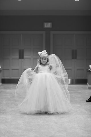 black-and-white-photo-of-a-flower-girl-in-a-dress-with-straps-and-a-tulle-skirt
