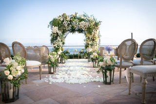 beautiful-ceremony-with-ocean-view-white-flower-petals-aisle-runner-lanterns-white-roses-greenery