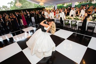 wedding tent reception black white checker dance floor groom dips bride for kiss romantic photo
