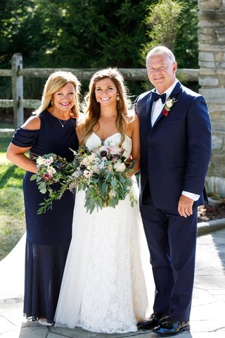 bride-in-strapless-lace-wedding-dress-with-rustic-chic-bouquet-mother-and-father-of-bride-in-navy