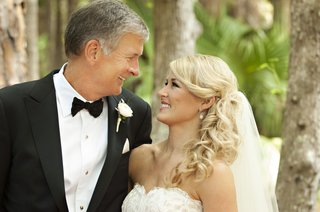 bride-in-a-veil-hugs-her-father-in-a-black-tuxedo