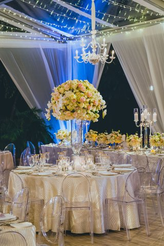tented-reception-with-ghost-chairs-patterned-linens-large-centerpieces-with-roses-and-orchids
