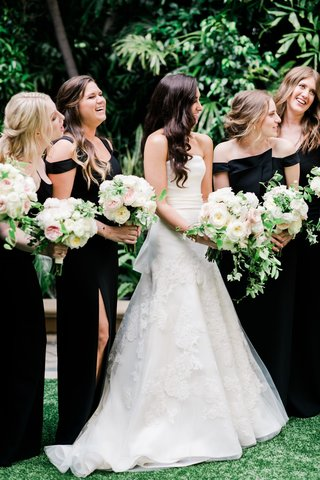 bride in vera wang wedding dress with bow detail in back bridesmaids in black dresses long slit