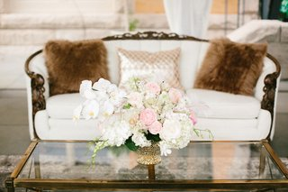 cream-sofa-with-fur-pillows-glass-table-with-florals-blue-garden-roses-white-orchids