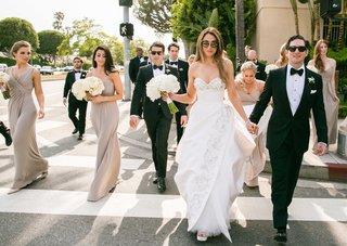 bride-in-oscar-de-la-renta-wedding-dress-groom-in-tuxedo-bridesmaids-groomsmen-walking-in-street