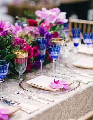 outdoor-wedding-with-colorful-low-flower-centerpieces-clear-gold-rim-charger-with-orchid-bloom