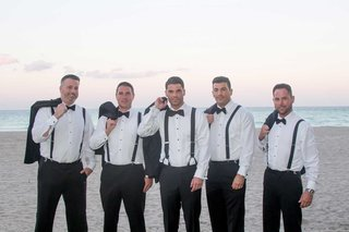 groom-and-groomsmen-with-jackets-over-shoulders-white-shirts-bow-ties-black-suspenders-sunset
