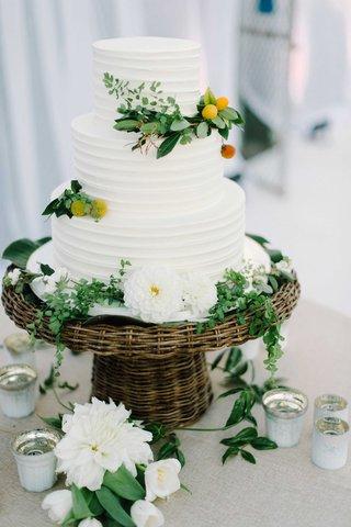 three-tier-white-wedding-cake-greenery-wicker-flowers-candles-leaves-oceanside-california-wedding