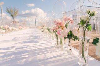 white-aisle-runner-lined-with-crystal-vases-filled-with-pink-and-white-roses-outdoor-wedding