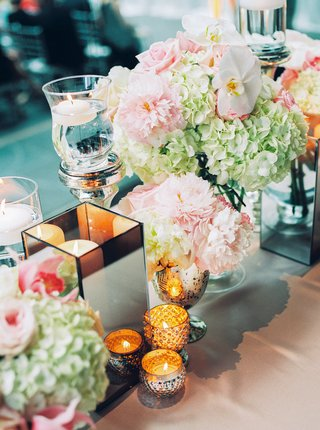 low-floral-arrangements-hydrangeas-orchids-pink-white-small-candles-box-vessel-white-linen