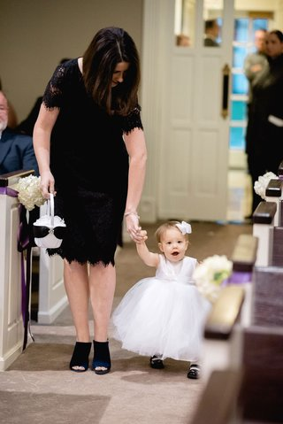 woman-in-black-lace-dress-and-peep-toe-booties-helping-baby-flower-girl-walk-down-aisle-ceremony